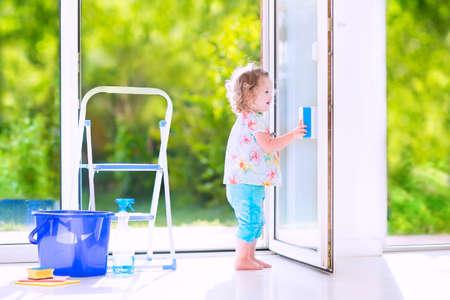 Risa linda niña niño rizado lavar una gran ventana con una escobilla de goma en la hermosa sala de estar blanca con puerta al jardín, de pie en una escalera junto a un cubo azul con agua, botella de detergente spray de solución y esponja