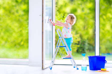 Cute laughing curly toddler girl washing a big window with a squeegee in beautiful white living room with door into the garden, standing on a ladder next to a blue bucket with water, detergent solution spray bottle and sponge Stock Photo
