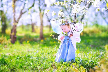 angeles bebe: Muchacha adorable del niño con el pelo rizado y una corona de flores que llevaba un traje de hada mágica con un vestido azul y alas de ángel jugando en un soleado jardín de árboles frutales en flor con flores de cerezo y los manzanos Foto de archivo