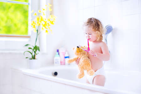 Happy funny baby girl wearing a diaper brushing her teeth and playing with her teddy bear toy and a toothbrush in a bathtub after shower in sunny white bathroom with window photo