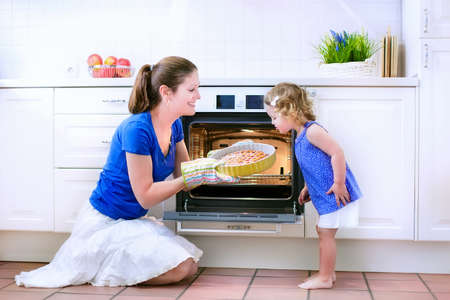 blue white kitchen: Young happy mother and her adorable curly toddler daughter wearing blue dress baking a pie together in an oven in a white sunny kitchen with modern appliances and devices Stock Photo