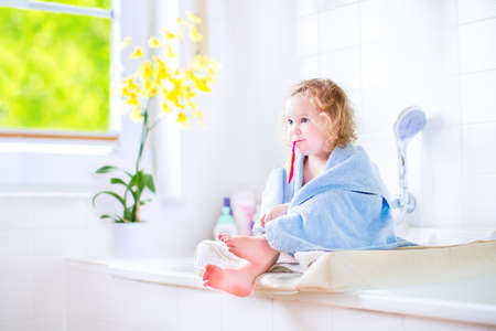big teeth: Funny toddler girl with curly hair and big eyes in a blue hooded towel after shower sitting in a white sunny bathroom brushing her teeth next to a window