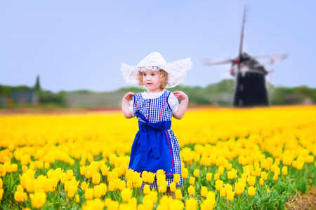 Adorable curly toddler girl wearing Dutch traditional national costume dress and hat playing in a field of blooming tulips next to a windmill in Amsterdam region, Holland, Netherlands photo