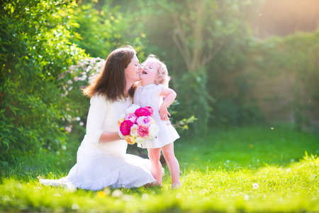 Beautiful young mother nd her adorable little daughter, cute little curly girl in a white dress, playing in the garden, hugging and kissing, with a bunch of red and pink flowers on a sunny summer day