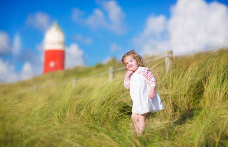 dutch girl: Funny toddler girl having fun on a beach with a beautiful red lighthouse on the island Texel, Holland, Netherlands, playing with sand on a windy sunny summer day Stock Photo