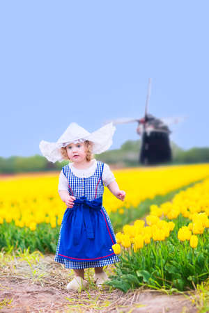 dutch windmill: Adorable curly toddler girl wearing Dutch traditional national costume dress and hat playing in a field of blooming tulips next to a windmill in Amsterdam region, Holland, Netherlands Stock Photo