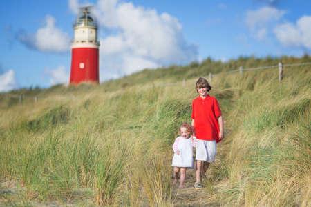De gelukkige kinderen, jonge actieve jongen en zijn schattige krullend zusje draagt een jurk spelen met zand speelgoed op een zonnige winderige strand met een rode vuurtoren op Texel, Holland, Nederland
