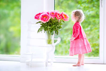 Toddler girl playing with peony flowers Stock Photo