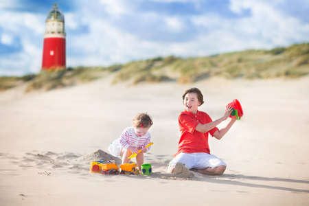 dutch girl: Happy children, young active boy and his adorable curly baby sister wearing a dress playing with sand toys on a sunny windy beach with a red lighthouse on Texel island, Holland, Netherlands