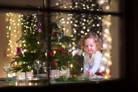 Cute curly toddler girl standing at a Christmas dinner table settling the glasses and dishes preparing to celebrate Xmas Eve, view through a window from outside into a decorated dining room with tree and lights