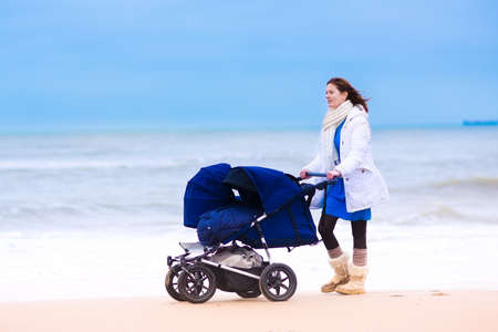 Happy active young mother walking on a beach pushing an all terrain doublt stroller with two kids, baby and toddler, on a cold winter day in Holland photo
