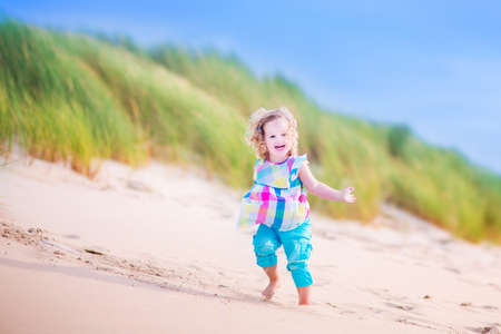 north holland: Happy funny little girl, adorable curly toddler, running and jumping in sand dunes enjoying family vacation at the North Sea, Holland, Netherlands on a hot sunny summer day at the beach