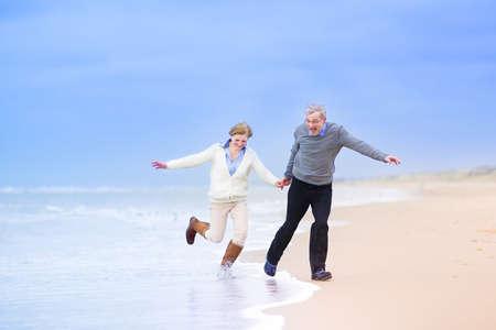 Gelukkig echtpaar van middelbare leeftijd, mooie actieve vrouw en een lachende man die op een strand jumpng weg van golven op de Noordzee, Scheveningen, Holland