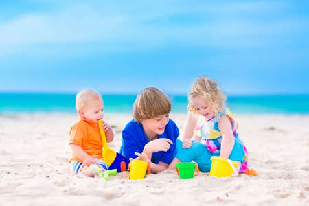 Three kids, teen age boy, little toddler girl and a funny baby playing together digging in sand with plastic colorful toys, spade and buckets, relaxing on a sunny tropical beach during family summer vacation