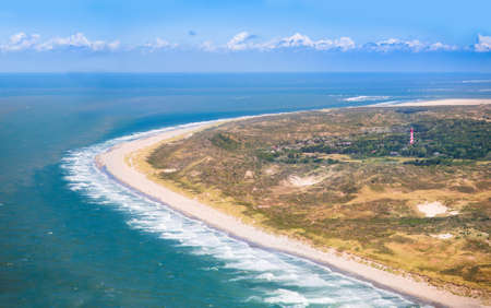 north holland: Aerial view of sand dunes and beach with a red and white lighthouse in Zeeland, Netherlands, taken from above on a helicopter trip Stock Photo
