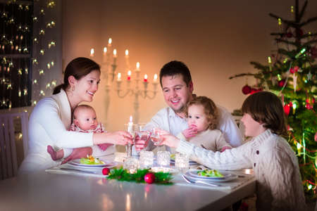 Big happy young family with three children enjoying Christmas dinner celebration, parents and kids - teen age boy, little toddler girl and baby in a dark dining room wth candles and xmas tree Stock Photo