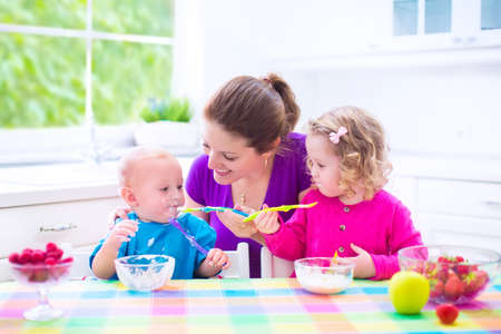 창 흰색 햇볕이 잘 드는 부엌에 앉아 행복 한 젊은 가족, 두 아이, 건강한 아침을 먹고 과일과 유제품 가진 사랑스러운 유아 소녀와 재미 아기와 어머니