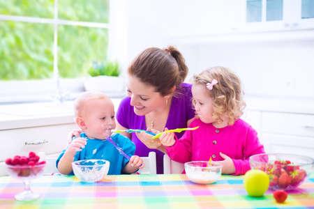 Heureux jeune famille, mère de deux enfants, fille adorable bambin et drôle petit garçon le petit déjeuner saine alimentation fruits et les produits laitiers, assis dans une cuisine ensoleillée blanc avec fenêtre Banque d'images