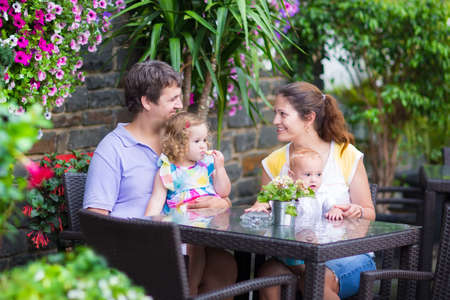 Happy young family, parents with two children, adorable little girl and a funny baby boy, eating lunch in a beautiful outdoor cafe with flowers in a city center on a warm summer day