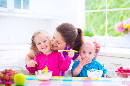 niños desayunando: Feliz joven familia, madre de dos hijos, niña adorable niño y bebé desordenado divertido que desayuna sano comer frutas y lácteos, sentado en una cocina blanca soleada con ventana
