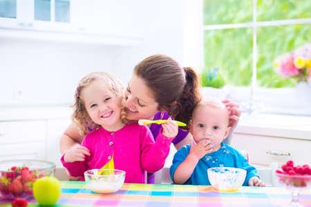 bambin: Heureux jeune famille, m�re de deux enfants, adorable bambin fille et dr�le petit gar�on malpropre ayant sain petit-d�jeuner de fruits de l'alimentation et les produits laitiers, assis dans une cuisine ensoleill�e blanc avec fen�tre