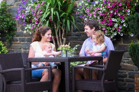 Happy young family, parents with two children, adorable little girl and a funny baby boy, eating lunch in a beautiful outdoor cafe with flowers in a city center on a warm summer day photo