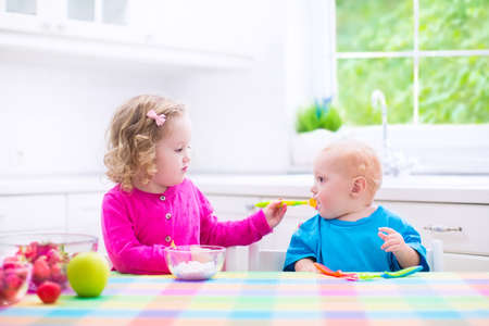 having breakfast: Two little children, adorable toddler girl and funny baby boy, eating yoghurt with berry and fruit together, sister feeding the brother, having healthy breakfast in a white sunny kitchen with window Stock Photo