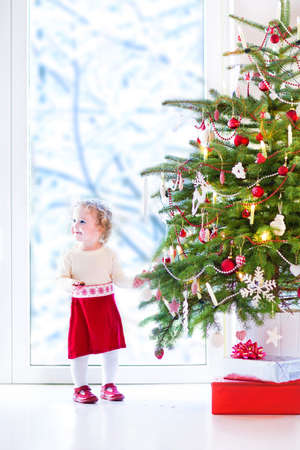 Adorable little toddler girl with curly hair in a warm knitted dress decorating a beautiful Christmas tree at a big window with a view of a snowy garden photo
