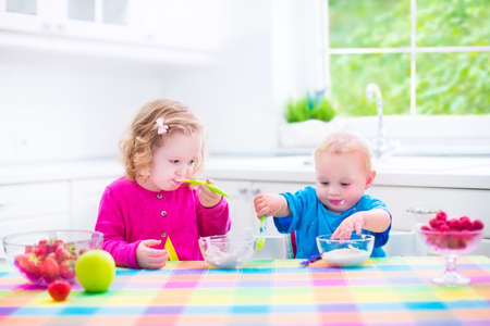solid food: Two little children, adorable toddler girl and funny baby boy, brother and sister, eating yoghurt with berry and fruit together having healthy breakfast in a white sunny kitchen with window Stock Photo