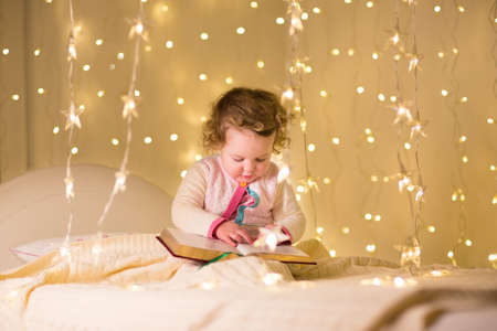 Cute little toddler girl reading a book in a dark room with Christmas lights  photo