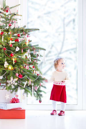 Adorable toddler girl in a warm knitted dress decorating a beautiful Christmas tree at a big window with a view of a snowy garden  photo
