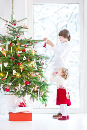 Adorable toddler girl with curly hair wearing a warm red dress helping her brother to decorate a beautiful Christmas tree standing next to a big window with a view of a snowy garden  photo