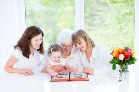 Happy grandmother watching black and white photo album with her daughter and grandchildren in a beautiful white dining room with a big garden view window
