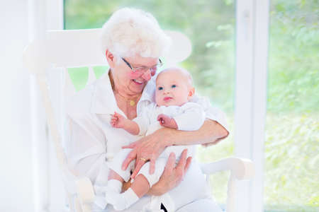 Loving grandmother singing a song to her newborn baby grandson sitting in a white rocking chair next to a big garden view window  Standard-Bild