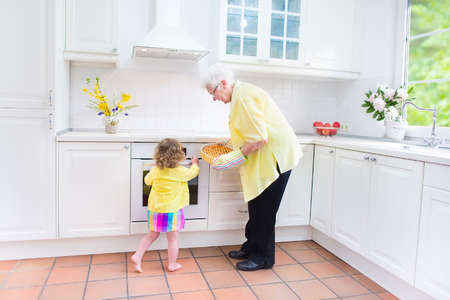 Happy grandmother and little girl baking a pie in a white kitchen photo