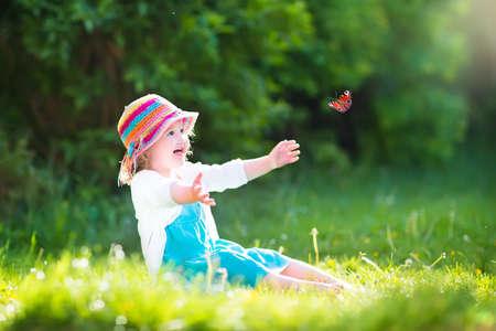 Glückliche lachende kleine Mädchen trägt ein blaues Kleid und bunten Strohhut spielen mit einem fliegenden Schmetterling Spaß im Garten an einem sonnigen Sommertag Standard-Bild - 30965910