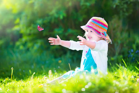 butterfly hand: Happy laughing little girl wearing a blue dress and colorful straw hat playing with a flying butterfly having fun in the garden on a sunny summer day