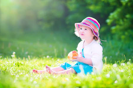 Happy beautiful little girl wearing a blue dress and colofrul straw hat eating a big fresh apple as healthy snack sitting on a lawn playing in a sunny summer garden photo