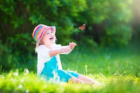 Gelukkig lachend meisje draagt een blauwe jurk en kleurrijke strooien hoed spelen met een vliegende vlinder plezier in de tuin op een zonnige zomerdag
