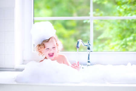 bathtub: Funny little baby girl with wet curly hair taking a bath in a kitchen sink with lots of foam playing with water drops and splashes next to a big window with garden view Stock Photo