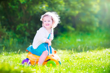 family garden: Happy laughing toddler girl in a blue dress having fun playing in the garden riding a yellow toy car enjoying sunny weather on a warm windy summer day