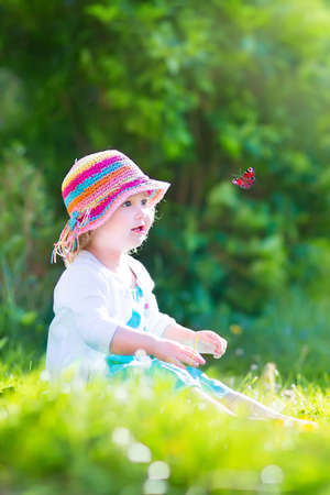 hand butterfly: Happy laughing little girl wearing a blue dress and colorful straw hat playing with a flying butterfly having fun in the garden on a sunny summer day