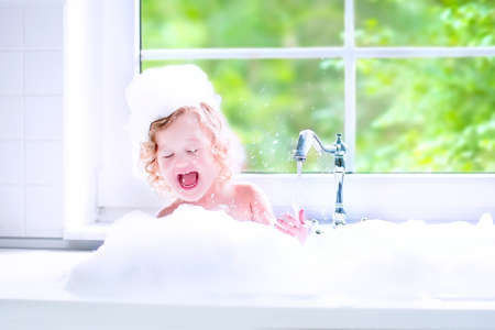 Funny little baby girl with wet curly hair taking a bath in a kitchen sink with lots of foam playing with water drops and splashes next to a big window with garden view Banque d'images