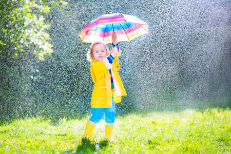 Funny cute curly toddler girl wearing yellow waterproof coat and boots holding colorful umbrella playing in the garden by rain and sun weather on a warm autumn or sumemr day Standard-Bild
