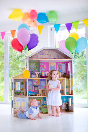 Adorable curly toddler girl in a white dress and her little baby brother playing together with a birthday present - huge doll house in a white living room with big windows decorated with balloons