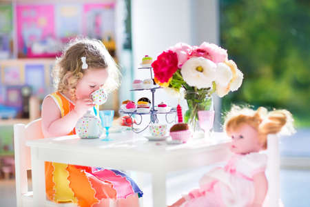 baby doll: Adorable toddler girl with curly hair wearing a colorful dress on her birthday playing tea party with a doll, toy dishes, cup cakes and muffins in a sunny room with window