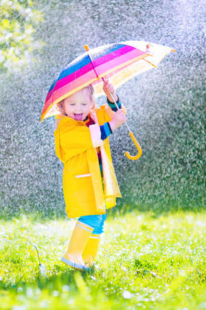 Funny cute curly toddler girl wearing yellow waterproof coat and boots holding colorful umbrella playing in the garden by rain and sun weather on a warm autumn or sumemr day Stock Photo