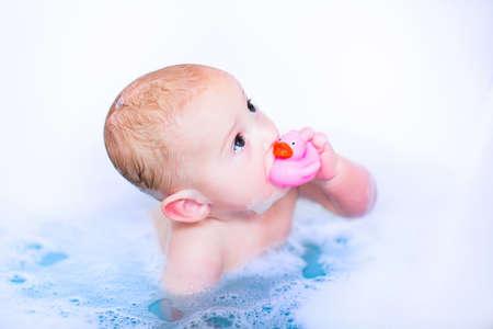 Mignon petit garçon Takin un bain moussant avec de la mousse de jouer dans l'eau avec un jouet de canard en caoutchouc après la douche Banque d'images - 30965969