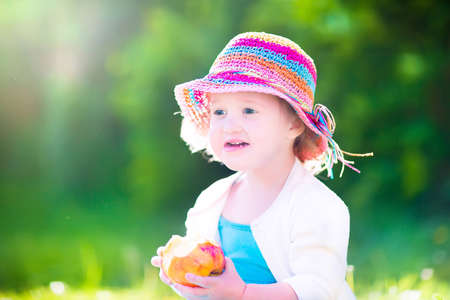 Funny happy toddler girl in a colorful straw hat and blue dress eating a big fresh apple as healthy snack for lunch playing in a sunny summer garden photo