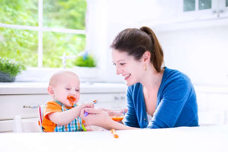 plastic spoon: Young attractive mother feeding her cute baby son, giving him his first solid food, healthy vegetable pure from carrot with a plastic spoon sitting in a white sunny kitchen at a window at home